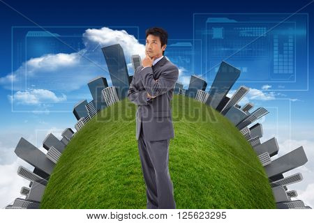 Thoughtful businessman with the arms crossed against bright blue sky with clouds