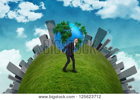 Businessman carrying the world against painted sky