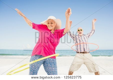 Senior couple doing hula hoop on the beach
