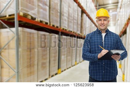 wholesale, logistic, business, export and people concept - happy man or manager in helmet with clipboard and pencil checking goods over warehouse background