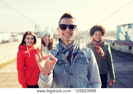 people, friendship and international concept - happy young man or teenage boy in front of his friends showing ok sign on city street