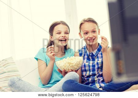people, children, television, friends and friendship concept - two happy little girls watching comedy movie on tv and eating popcorn at home