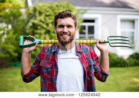 Portrait of smiling man carrying rake while standing in yard