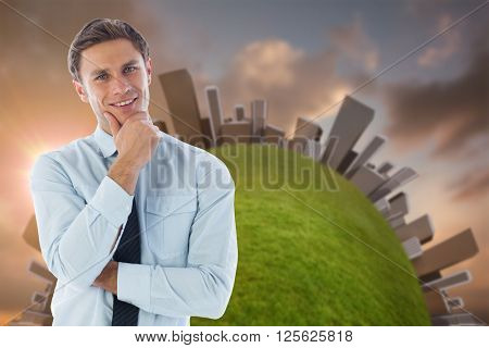 Thinking businessman with hand on chin against blue and orange sky with clouds