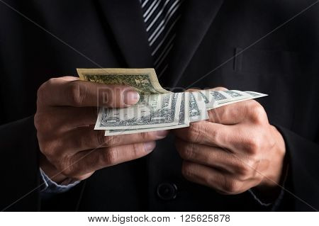 business concept Businessman counting money stack of dollars in hands