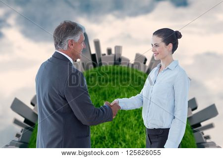 Business people shaking hands against painted sky