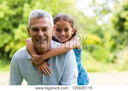 Smiling grandfather carrying grandaughter in yard