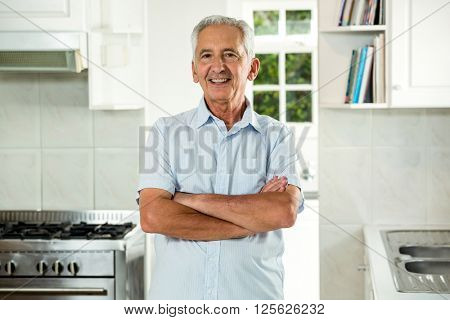 Portrait of smiling senior man with arms crossed while standing in kitchen