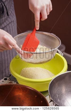 hands sifts flour in to bowl for cake baking