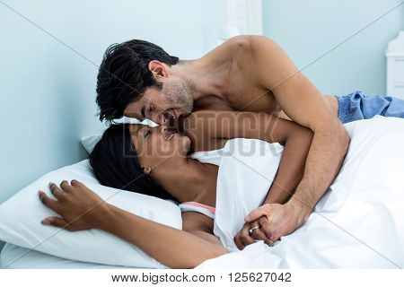 Young couple embracing while lying on bed in bedroom