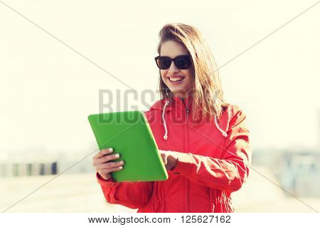 technology, lifestyle and people concept - smiling young woman or teenage girl with tablet pc computer outdoors