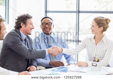 Businessman shaking hands with businesswoman in meeting at office