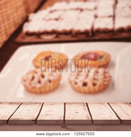 Wooden desk against close up of basket with fresh bread and pastry Close up of basket with fresh bread and pastry at the bakery