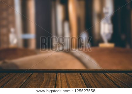 Close-up of wooden flooring against wooden barrels of wine fermenting