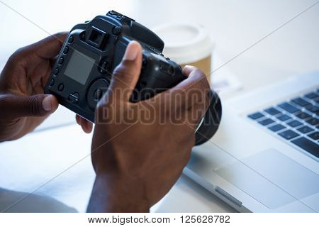 Man checking photo in camera in office
