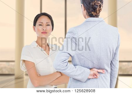 Businesswoman with fingers crossed behind her back over white background against window overlooking city