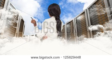 Thinking businesswoman against blue sky with white clouds