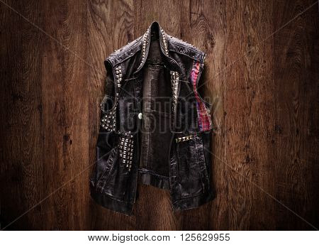 Old-school punk-rock leather jacket hanging on a wooden background