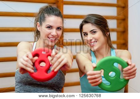 Portrait of two fit young women smiling in a exercise room holding weights - sport, fitness, lifestyle and people concept.