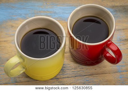 two stoneware cups of espresso coffee against grunge painted wood