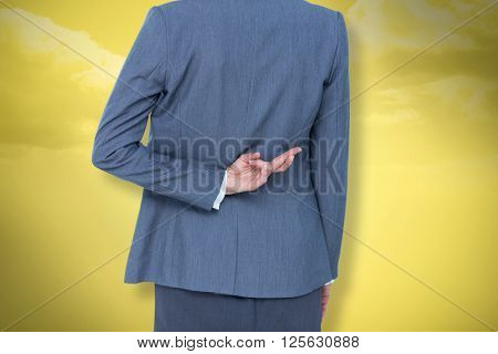 Businesswoman with fingers crossed behind her back against yellow background