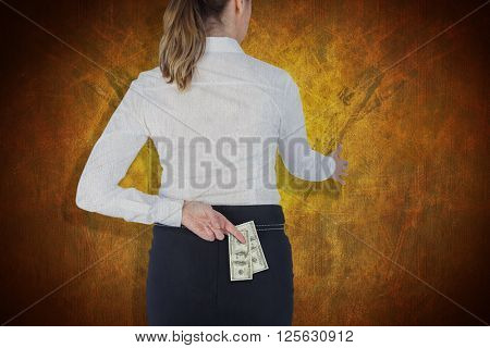 Businesswoman offering handshake with fingers crossed behind her back against dark background