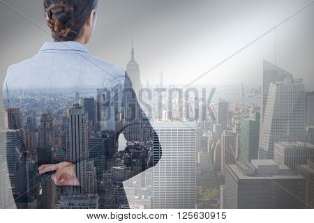 Businesswoman with fingers crossed behind her back over white background against city skyline