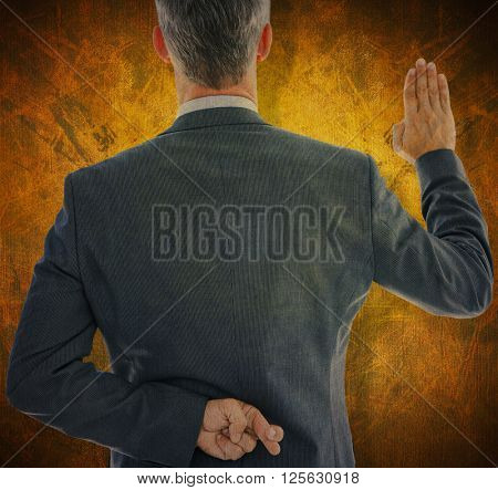 Rear view of businessman taking oath with fingers crossed against dark background
