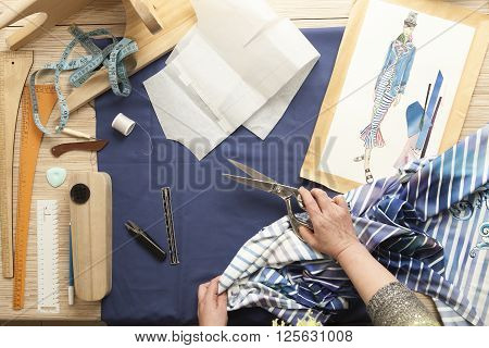 Desk designer fashion. Fashion designer starts cutting fabric to create fashionable clothes on the sketches.