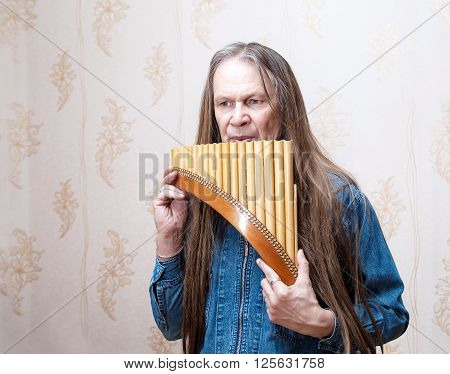 long-haired elderly man playing the pan flute closeup