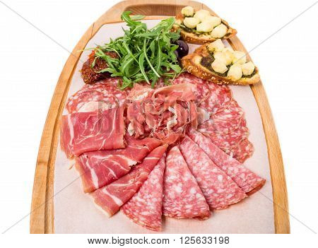 Traditional tuscan antipasto platter with cold cuts and dried tomatoes. Isolated on a white background.