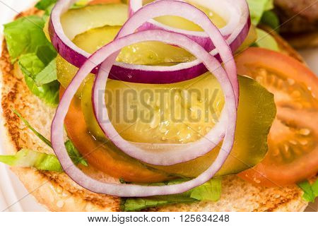 Closeup of burger bun with sliced red onion and pickled tomatoes on lettuce leaves. Macro. Photo can be used as a whole background.