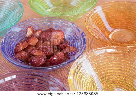 strawberry salad in a sequence of colored glass bowls