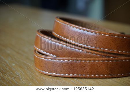 Brown leather band with white stitching on the wooden desk
