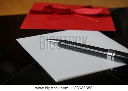 Black pen writing announcement letter with the red envelope on the wooden desk