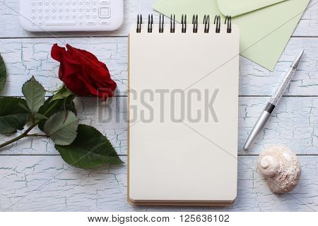 Mockup for presentations with red rose notebook and a pen. Desktop workplace designer artist painter top view. Modern trend template for advertising.
