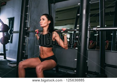 brunette young sports woman doing squats with a barbell in Smith machine at the gym, front view