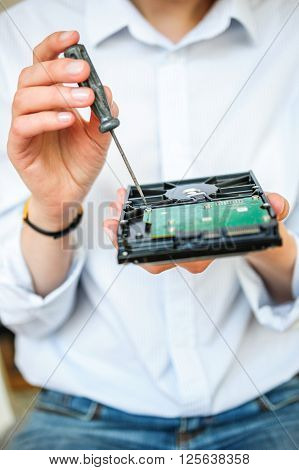 IT specialist hands holding HDD with screwdriver on it trying to repair the damaged computer disk