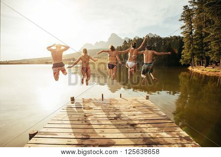 Portrait of young people jumping from pier into lake together. Friends jumping off the jetty at the lake on a sunny day.