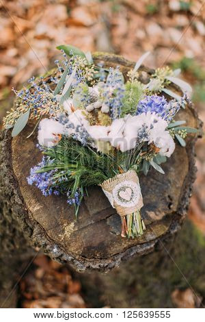Beautiful wedding bouquet of colorful spring flowers on the stump in forest.