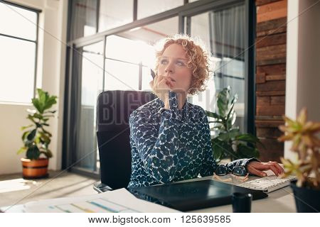 Portrait of young female designer sitting at her desk looking away and thinking.