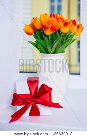 Close Up Of Beautiful Orange Tulips And Gift Box On A Window Sill