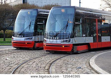 PRAGUE, CZECH REPUBLIC - CIRCA MARCH 16: Two brand new trams on the parallel cobbled tracks in Prague, Czech republic