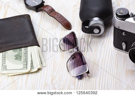 gentlemanly set:  sunglasses, perfume, wallet with money, camera and watch on wooden background