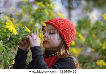 Little girl with red cap sniffing flowers.  Girl in a red dress.