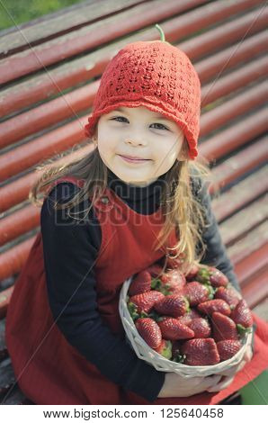 Girl with strawberries. Little girl eating a strawberry. Girl with a red hat.
