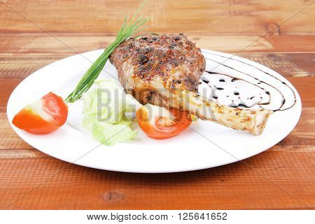 meat savory on table : roast shoulder with tomato and chives over white plate