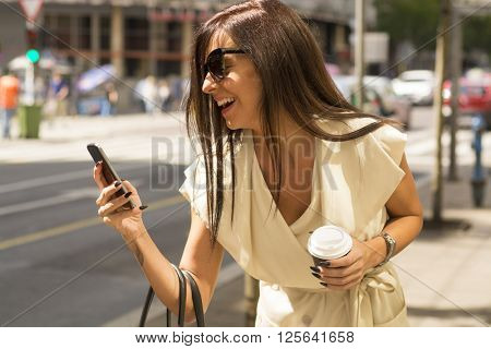 Fashionable young brunette wearing white dress and sunglasses laughs into phone on city street