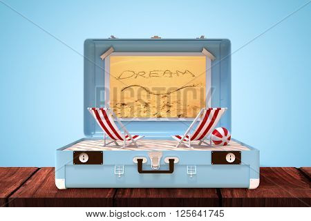Image of a suitcase against inscription dream on sand