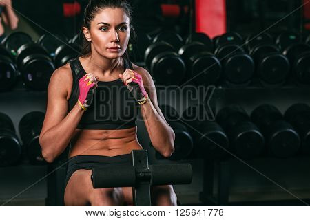 fitness brunette woman doing abdominal crunch in gym woking out